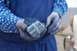 Les mains d'un teinturier-imprimeur autrichien tenant deux blocs de pigment indigo indien  © Catherine Legrand